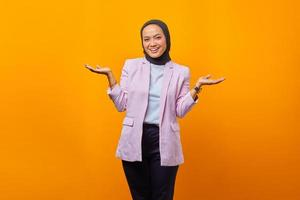 Cheerful Asian woman showing product over yellow background photo