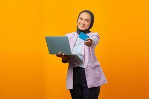 Cheerful young woman standing holding laptop and showing credit card photo