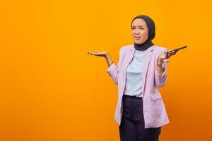 Portrait of young angry Asian woman raising palms confusedly photo