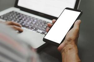 Man hand holding a blank screen mockup smart phone photo