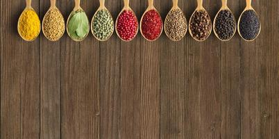 Various spices and herbs in wooden spoons photo