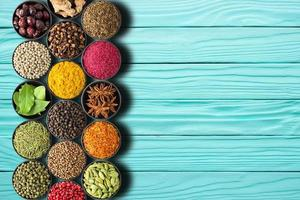 Set of seasonings on a turquoise table with empty space photo