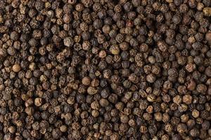 especias de granos de pimienta negra como fondo foto