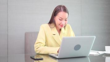 Young asian woman uses a laptop video