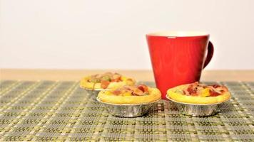 Tasty egg tart pizza and red cup coffee concept photo