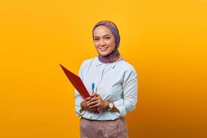 Beautiful Asian woman holding folders and pen looking at camera photo