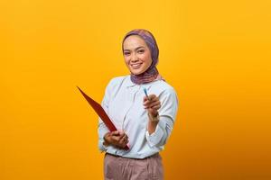Beautiful Asian woman holding folders and pointing with pen photo