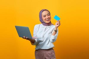 Cheerful Asian woman holding laptop and looking blank card photo