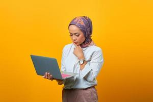 Beautiful Asian woman holding laptop with serious expression photo
