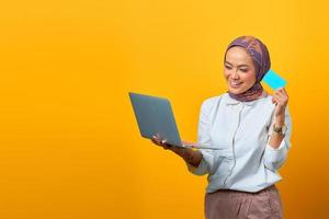 Cheerful Asian woman holding laptop and showing blank card photo