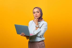 Portrait of confident Asian woman holding laptop and looking at camera photo