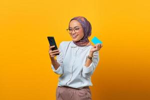 Cheerful Asian woman holding smartphone and showing blank card photo