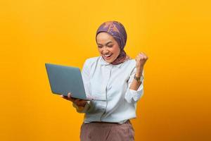 Portrait of excited Asian woman holding laptop photo
