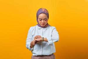 Beautiful Asian woman checking time on watch over yellow background photo