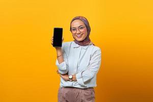 Cheerful Asian woman showing smartphone blank screen photo