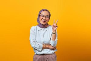 Portrait of cheerful Asian woman showing peace sign photo