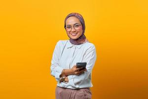 Smiling Asian woman holding mobile phone with crossed arms photo