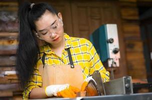 La mujer es artesanía trabajando madera cortada con sierras circulares herramientas eléctricas foto