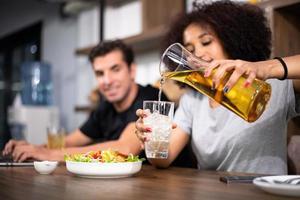 pareja joven está alimentando mientras se cocina la ensalada foto
