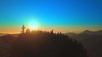 cruz de uma montanha passando zumbindo o pôr do sol video