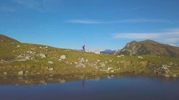 Una niña va de excursión a los prados de las montañas cerca de un lago. video