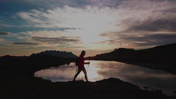 una niña en una montaña camina al atardecer video