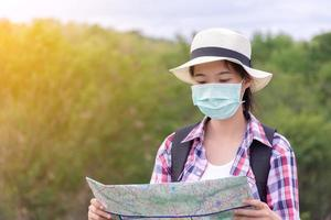 Girl backpacker traveler wearing facial mask and looking map photo