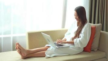 Young asian woman uses a laptop on the couch video