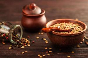 Lentils in a clay vessel on and wooden spoon on a wooden background photo