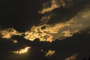 nubes oscuras, nubes de tormenta y sol que estalla foto