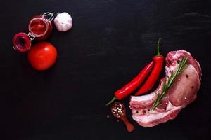 entrecot de cerdo carne cruda con romero, pimiento y salsa roja foto