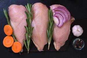 Fillet of chicken breast with rosemary, carrots, garlic and onions photo