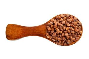 Buckwheat in a wooden spoon on a white background photo
