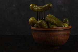 Gherkins and sauerkraut in a clay bowl on a dark concrete background photo