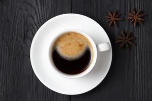 Hot coffee with foam in a white cup with anise photo