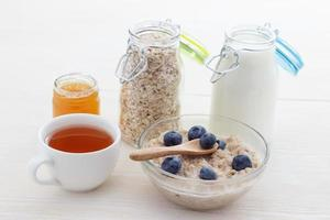 Healthy eating oat flakes of blueberries and tea with honey photo