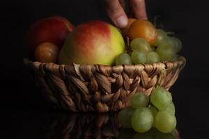 Fruits of grapes, plums and an apple in a wicker basket photo