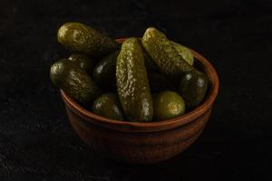 Cucumbers in a clay bowl on a dark concrete background photo