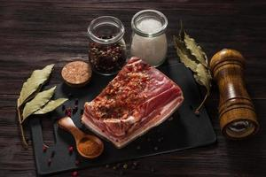 Salted bacon with spices and bay leaves and a mill photo