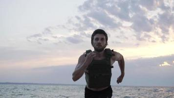 Young bearded athlete training outdoor with weighted vest video