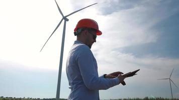 mannelijke werknemer in helm kijken op de windturbine video