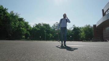 jovem empresário barbudo do sexo masculino andar de skate ao ar livre video