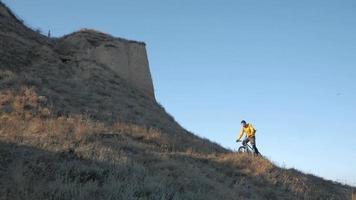 jeune homme cycliste voyage sur les collines en journée ensoleillée d'été video