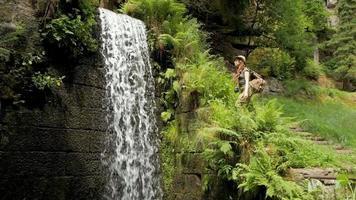 jeune femme randonneur avec sac à dos près de la cascade dans les montagnes video