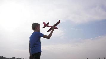Male boy play with toy airplane in summer fields video