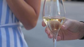 Cerca de una copa de vino espumoso en manos de mujer video