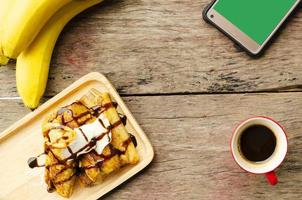 Banana french toast and Black coffee red cup and smartphone photo