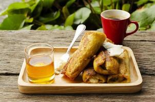 Banana French toast and Hot coffee drinks on wood table background photo