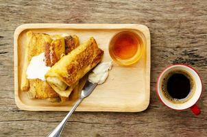 Banana French toast with honey on wood table backgrounds above photo
