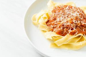 Pork bolognese fettuccine pasta with parmesan cheese photo